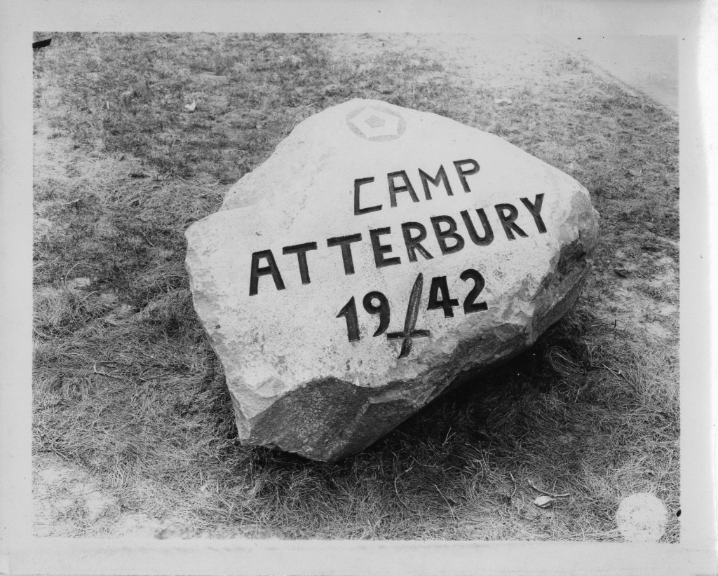 Rock at the junction of Edinburgh Street and Hospital Road near the entrance of Camp Atterbury, June 24, 1943. The limestone rock is carved with the name of the army base and the year of its founding. The insignia of the 5th Service Command is painted at the top.